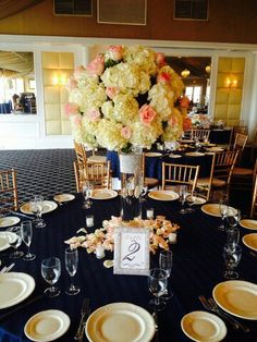 Clear cylinder with diamond band with white hydrangea and peach rose topper surrounded by rose petals. doristhefloristt.com