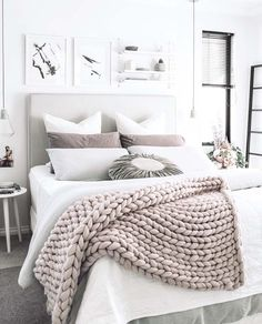 A chunky knit wool throw adds texture and interest to a gray and white bedroom.