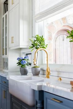 Blue kitchen cabinets with an antique brass gooseneck faucet display a dual farmhouse sink under a roman shade kitchen window.