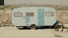 Rickety old vintage abandoned caravan/trailer in a deserted camp/area.An old rusty caravan near a pier close to an abandoned industrial camp. - 4K stock video clip