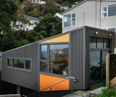 From the road, the black-aluminium-corrugate-clad house is hidden and very private. Looking up to it from the bay, a burst of orange on the exterior panelling. Photography by: David Straight. Exterior Paint, Exterior Design, Modern Garage, Narrow House, Architect House, Open Plan Living, Large Windows, One Bedroom, Home Projects
