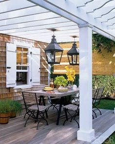 Shingled home exterior with white window trim and white painted pergola over the back porch.