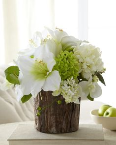 A unique tree-bark vase perfectly complements a beautiful arrangement of faux flowers in white and soft green.