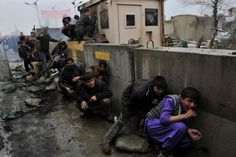 Afghan youth take cover from U.S. soldiers