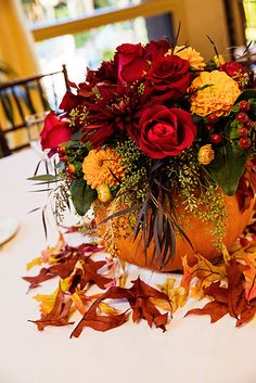 Add a hint of Halloween to your wedding reception with pumpkin floral centerpieces