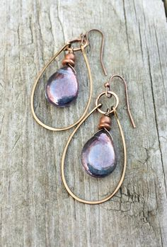 Purple iridescent Czech glass teardrop and antiqued copper hoop earrings One of my best selling designs! The hammered copper hoop with stunning, purple-blue iridescent Czech glass teardrops is one of my newer additions to this popular collection. These earrings add color while being