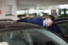 Man looking inside the car in a dealership ...  20s, Brown Air, Short Hair, analysing, automotive, black, businessman, buyer, car, classy, concentrated, dealer, dealership, elegant, file, folder, garage, happy, holding, indoors, looking, male, man, mixed-race, paper, salesman, serious, smart, smiling, sophisticated, standing, stylish, suit, tie, vehicle, well dressed, young adult