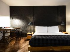 This+Ace+Hotel+bedroom+is+cozy,+yet+uncluttered.+The+black+wall+behind+the+platform+bed+adds+a+subtle,+stark+interest+to+the+space,+and+the+task+lighting+makes+everything+feel+utilitarian.