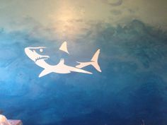 My son had a shark decal and he wanted it to be swimming in the ocean, not just a gray wall. Painted the ocean then removed the decal for a negative space