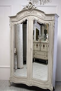 Country French closet with long mirrors on the doors.