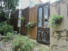 Privacy fence made from recycled doors. How cool is this?