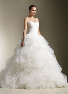 Justin Alexander Spring 2012 bridal collection. Strapless ball gown with sweetheart neckline, ruched tulle bodice, drop waist with full tulle pick up skirt accented with feathers
