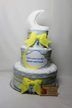 Baby Diaper Cake in a Love you to the Moon theme would be created with 50 Luvs sz. 1 diapers, 3 of my handmade 2-ply flannel burp cloths. Attached to a 12 faux silver scalloped edge cake plate, the diapers would be wrapped with the burp cloths and layered with yellow, blue and white grosgrain ribbons. Tier tops decorated with cotton balls. The front of the cake embellished with Love you to the moon and back, tell me if you want the babys name, if so leave at checkout. Wrapped in protective…