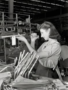 July 1942. Ford bomber plant at Willow Run, Michigan. Inspection of more than a thousand separate tubing pieces composing the fuel, hydraulic, de-icing and other systems in a bomber is a highly important job. This young employee at the giant Willow Run plant uses her tiny flashlight to discover any internal defects in the tubing. Photo by Ann Rosener, Office of War Information.