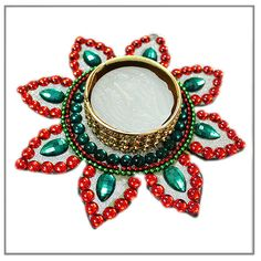 Flower Diya, Designer beautiful eye-catching wax diya in the shape of a Flower. Surrounded by Red and Green Stone.