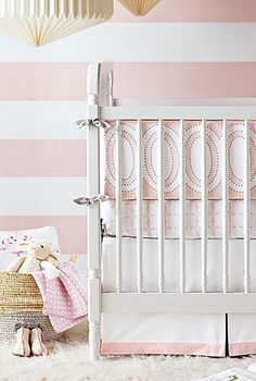 Beautiful nursery! Loving the striped wall and this pretty pink bedding!