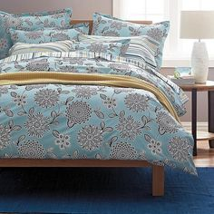 This earth-friendly organic cotton duvet cover is covered with stylized contemporary florals in graphic black and white against a pale blue sky.