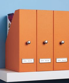 DIY-Knobs as file pulls~ Punch a hole in a cardboard magazine file, insert a cabinet knob and you have a much cuter magazine file that is also easier to take on and off of the shelf!