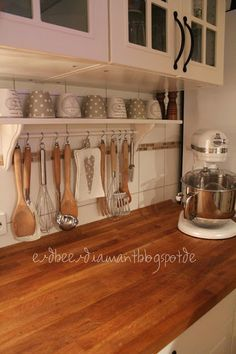 I like the shelf and little rod to hang utensils from. Seems like the distance between the countertop to lower cabinet is higher than normal?