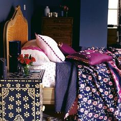 richly coloured bedroom in navy and purple. liking the color contrast with this headboard & the end table