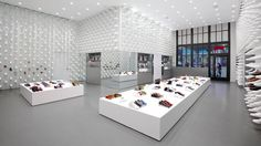 Camper's new store in NY by Oki Sato, founder of Nendo - Nendo's solution was to completely cover the walls in the store with white plastic replicas of Camper Pelotas, the brand's signature shoe design. The current collections are then displayed amongst these replicas in spaces at the base of the walls where customers are able to reach.