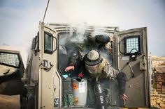 Credit: Hamde Abu Rahma/NurPhoto/Corbis Israeli soldiers flee their vehicle after teargas canisters exploded in it near Bilin in the West Ba...