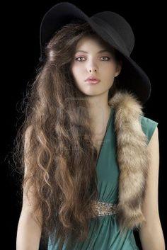 ritratto di donna sofisticata ed elegante con stile i capelli e indossa un abito verde e una coda di pelliccia, cappello nero Archivio Fotografico