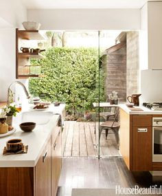 "In Mark Egerstrom's 1,200-square-foot West Hollywood home, the wood floors of the kitchen extend out to a coordinated deck through glass shower doors, creating the illusion of a much bigger space. The walnut cabinetry was designed by Egerstrom: ""It's my take on old farmhouse kitchens, updated to the 21st century."" It was fabricated by Gary Ferguson of Case and Grain with Glacier White Corian counters and custom inset handles."