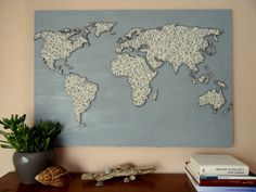 World map string art, white string on a light blue board.
