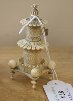 AN EARLY 19TH CENTURY CARVED IVORY TAPE MEASURE AND THIMBLE HOLDER
