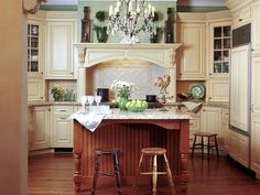 A Scoop of Vanilla Designer Gail Drury combined traditional sage-green accents and ivory cabinets, along with contemporary materials and conveniences, to bring an updated look and feel to this charming bungalow home. An eclectic mix of wood finishes in the island and barstools further add to the kitchen's old-fashioned appeal.