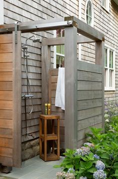 A gray teak outdoor shower boasts a gray teak door on rails and a polished nicke. A gray teak outdoor shower boasts a gray teak door on rails and a polished nickel shower kit and sprayer fixed over a tiered wooden accent table. Outdoor Baths, Outdoor Bathrooms, Outside Showers, Outdoor Showers, Outdoor Shower Kits, Outdoor Shower Enclosure, Casas Containers, Garden Shower, Outdoor Living