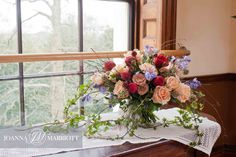 Nature inspired Bridal bouquet composed of red piano roses, soft peach roses, nude roses, blue bells and rustic foliage. #rusticwedding