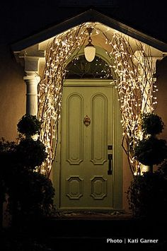 Using branches w/ lights by the front door (or other placement on the porch) for Christmas ~ beautiful!