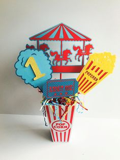 Celebrate a special birthday with this adorable Carnival Party Centerpiece. This centerpiece can make a perfect addition to any party décor. They look great right on gift or food tables, even right next to the cake! With this listing you will receive 4 pieces which include a popcorn, a carousel, ice cream cone with AGE, and ticket. For the centerpiece INCLUDING the popcorn bucket with the foam insert and confetti can be purchased at an additional charge. Just look to the drop down menu to th...