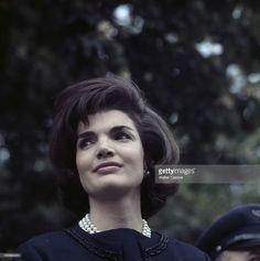 Jacqueline Kennedy In The Gardens Of At The White House. A Washington, en 1961, portrait de Jacqueline KENNEDY dans les jardins de la Maison Blanche, regardant vers la droite, portant une veste bleue et un collier de perles, à côté d'un officier militaire.