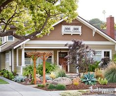 •Set the Scene Don't let your backyard have all the fun this year. Dial up the drama out front with an eye-catching landscape design. This Craftsman-style exterior transforms into an arid getaway thanks to sculptural plantings and an entry arbor.