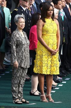 Michelle Obama wore a sunshine yellow Naeem Khan midi dress covered in laser-cut floral appliqués for a tour of the National Gallery of Art. FLOTUS finished the outfit with nude sandals. Get all the details!