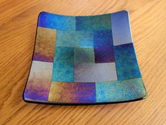 Iridescent fused glass dish made from transparent blue and