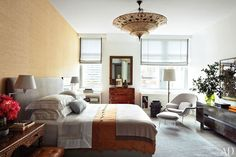 The master bedroom is illuminated by a Fortuny light fixture by Venetia Studium, an industrial floor lamp, and swing-arm sconces. The mirror dates from the 1950s, and the Eero Saarinen womb chair and ottoman are by Knoll; a framed heirloom Kuba cloth is mounted above the low cabinet at right. Pick up a copy of AD's February issue,