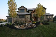 The front view of the Aspen Ridge I Floor Plan with a water feature in front.