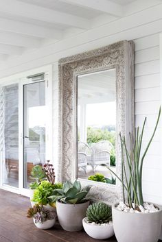 Concrete and white Pots with statement cactus / succulent plants and white pebbles set at the foot of this timber carved outdoor mirror. The Grove Byron Bay .