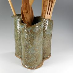 This 3 tube utensil holder is hand built stoneware clay. I rolled out slabs of clay with a rolling pin and wrapped around cardboard tubes. Each