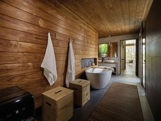 In this modern house, a walk-in dressing room is located between the master bedroom and the bathroom, while a door off the bathroom leads to a small private terrace. #Bathroom #Wood #ModernBathroom