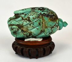 "Qing. Chinese carved turquoise buddha's hand citron snuff bottle with wood stand. size:31/8"" x 15/8"" was sold at Christies"