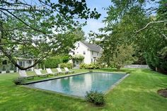 Classic clapboard house with a pretty pool area edged with grass