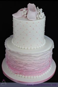 This ballet baby shower cake features an ombre ruffling technique on the bottom tier with custom made ballet shoes on top. A sweet way to welcome a little baby girl!
