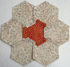 I have blogged since September 11, 2008 and on October 6, 2008 I wrote a tutorial about how to English Paper Piece hexagons using a glue stick and the freezer paper on the back of the fabric method…