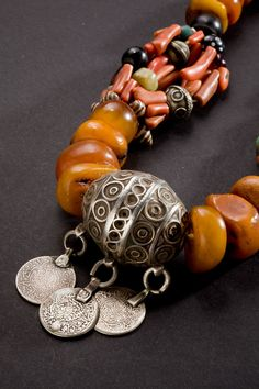 Morocco   Detail from a Berber necklace composed of silver, coral, glass, shells and a large oval silver tagemout bead with traces of enamel and coins as pendants. 1900