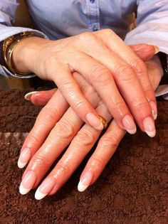 A French gel manicure on oval nails.